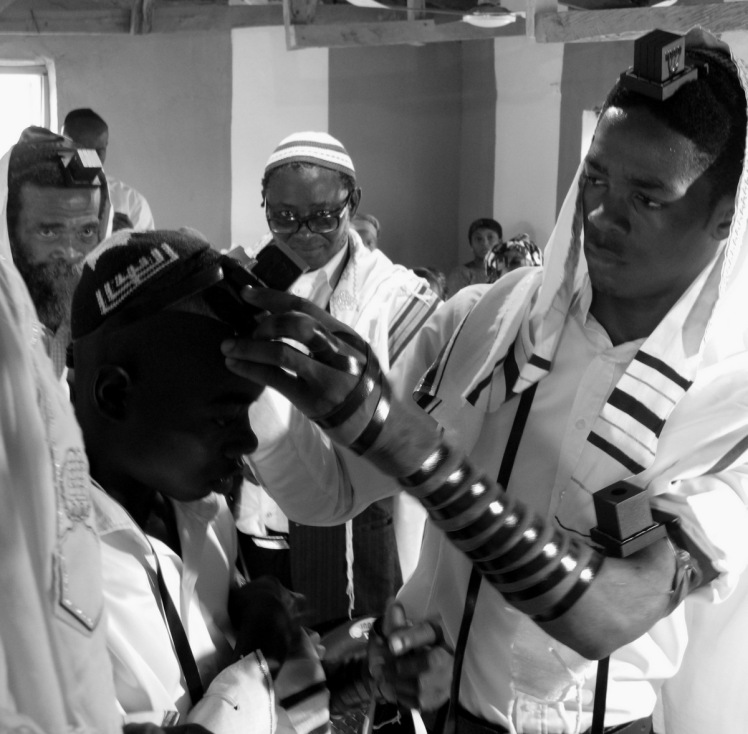 Hezekiah Nwafor helps Emmanuel Igwe don tefillin for the first time at Abuja's Tikvat Israel Synagogue. Photograph - Shai Afsai